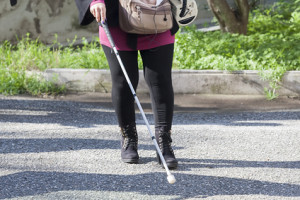 Close up of blind woman walking with a stick