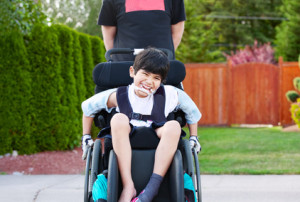 Young boy in wheel chair outside