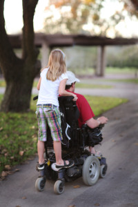 Young girl riding on the back of a man's wheelchair