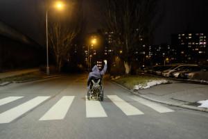 Man in wheel chair in crosswalk raising hand