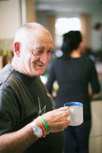 Elderly man holding mug of coffee smiling