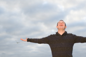 Young disabled man smiling outdoors looking at the sky