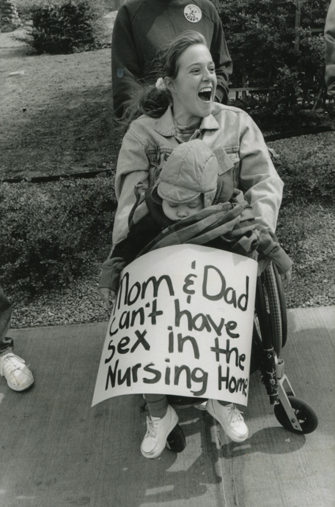 "Woman in wheelchair holding baby with sign that reads, ""Mom & Dad can't have sex in the Nursing Home"""
