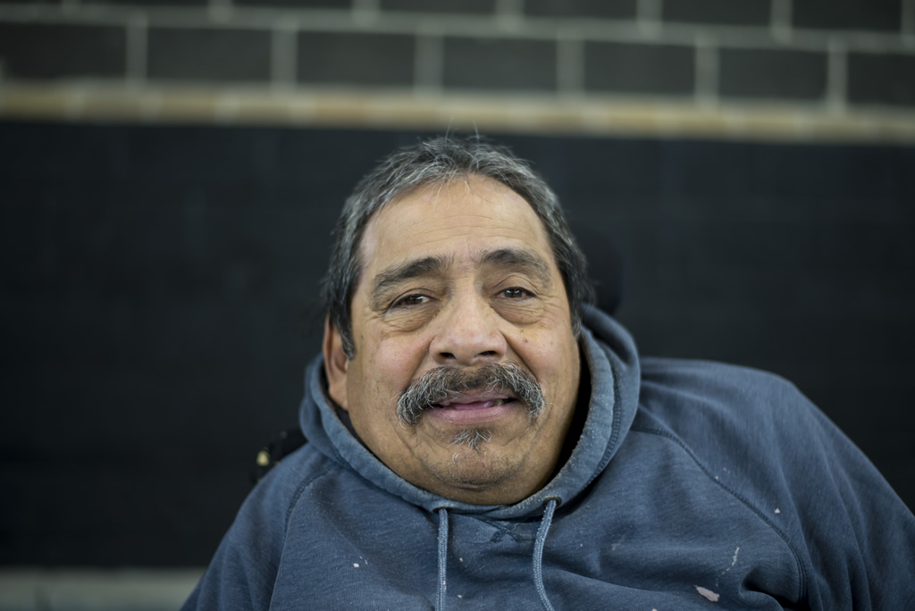 Man in a wheel chair with grey and black hair in grey hoodie looking at camera smiling