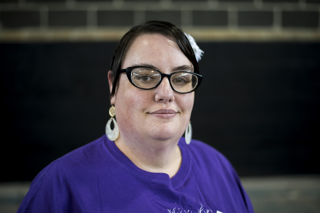Woman with short black hair and white earrings in purple Atlantis shirt looking at camera smiling