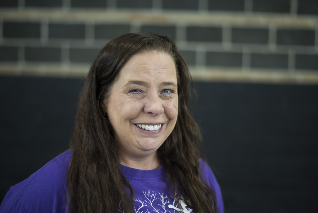 Woman with long dark brown hair in purple Atlantis shirt looking at camera smiling