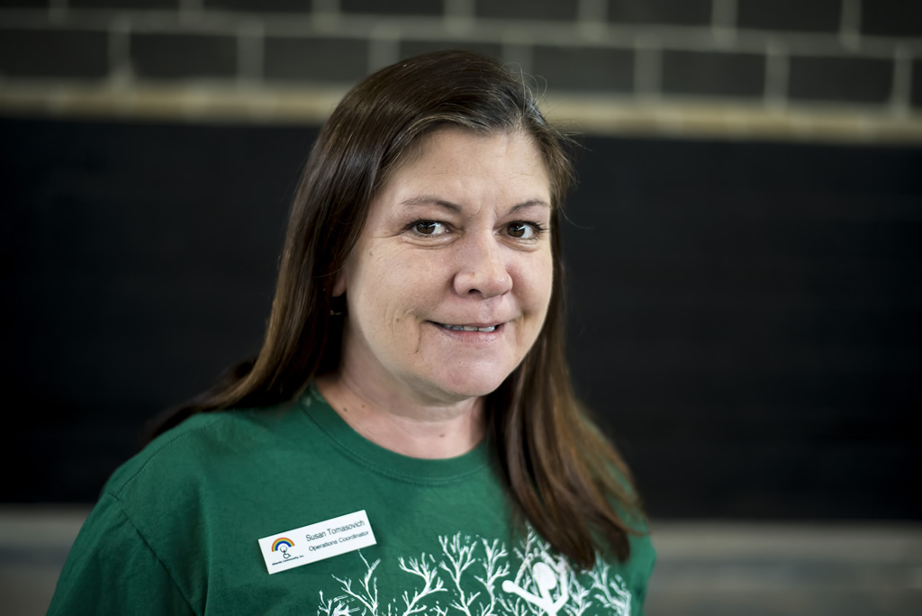 Woman with long dark brown hair in green Atlantis shirt looking at camera smiling