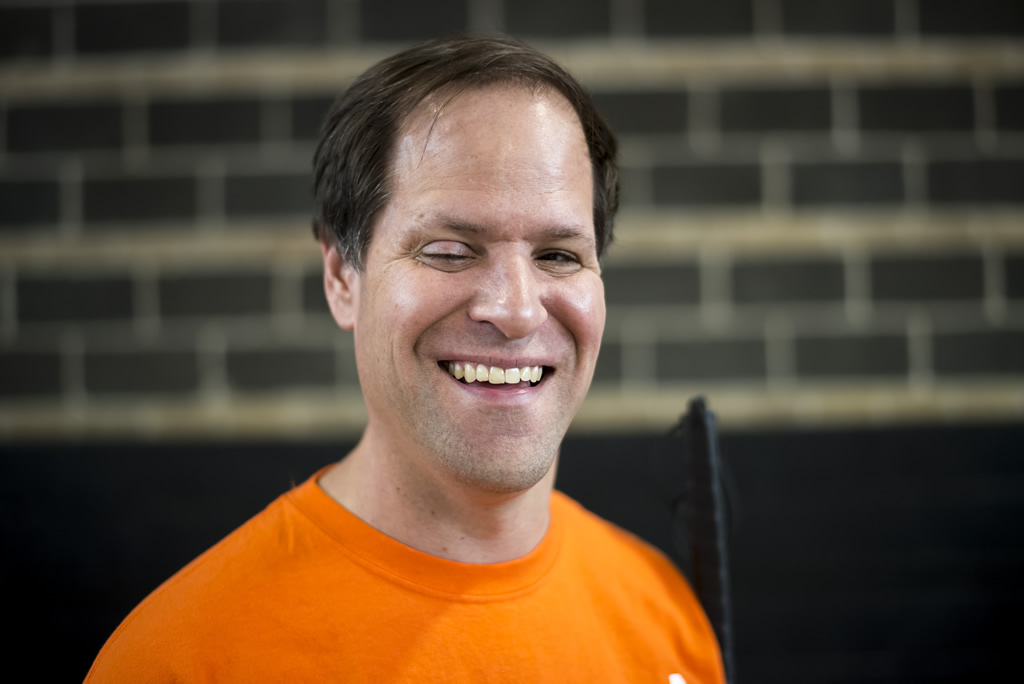 Man with short brown hair in orange Atlantis shirt looking at camera smiling