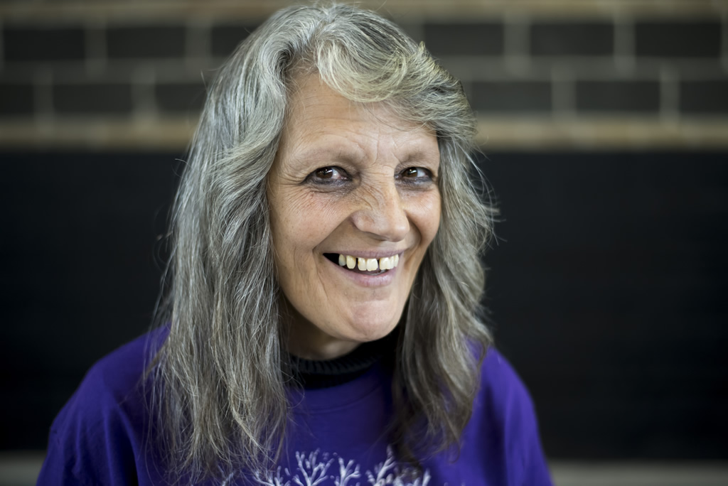 Woman with long gray and black hair in purple and black Atlantis shirts looking at camera smiling