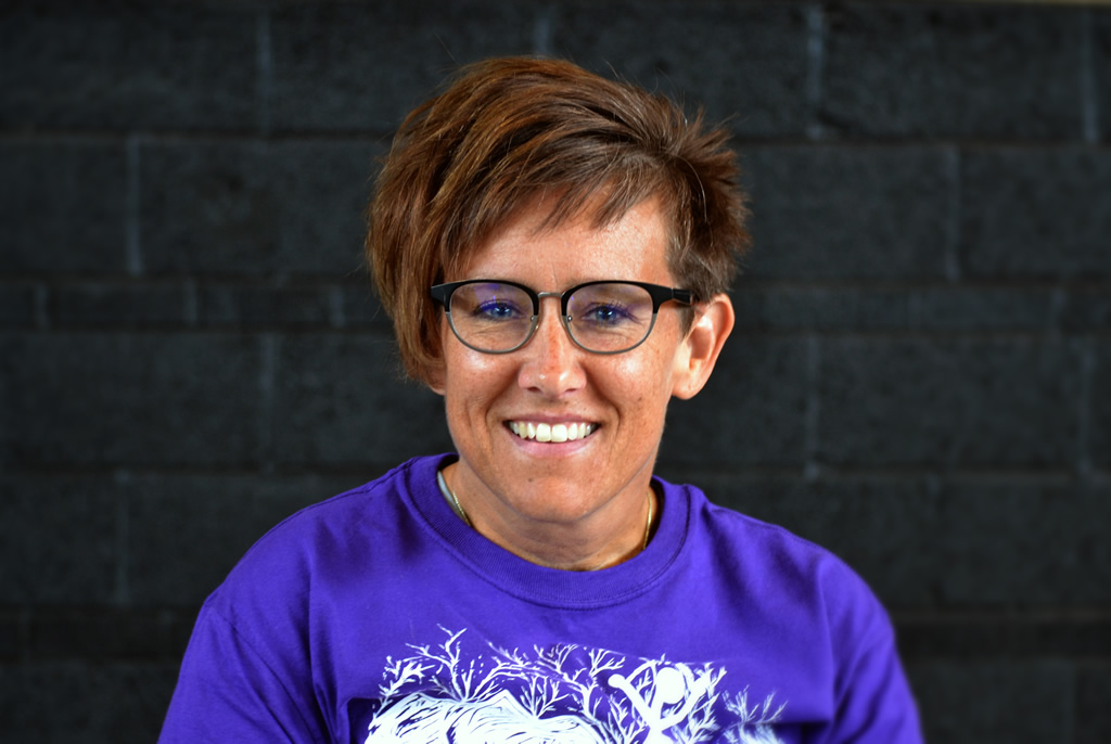 Woman in purple shirt looking at camera smiling