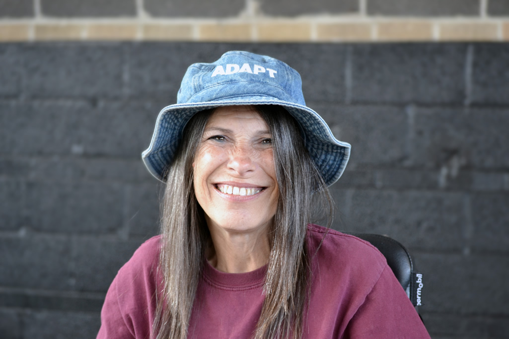 Woman wearing blue hat and maroon shirt