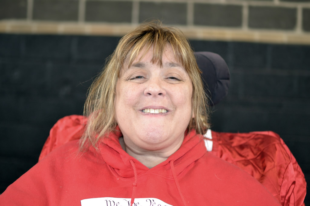 Woman with blonde brown hair in wheelchair wearing red hoodie smiling