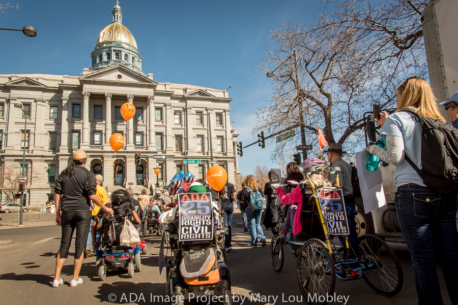 A picture of a group of people some in wheelchairs and some able bodied, with orange balloons and protest signs in front of the capital in Denver CO