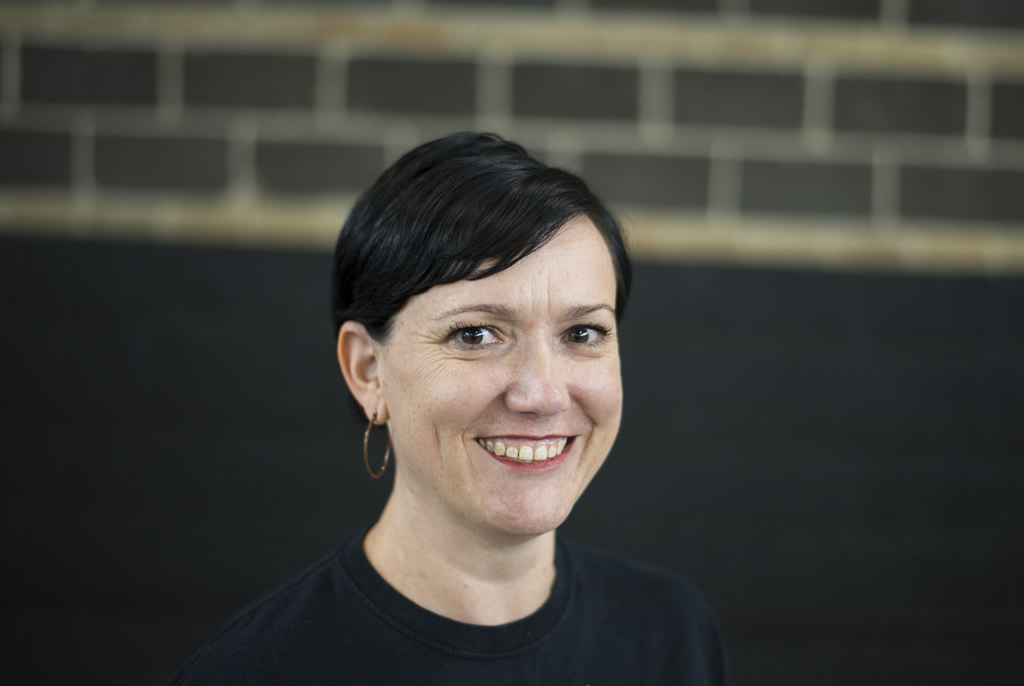 Woman with short black hair in black Atlantis shirt looking at camera smiling