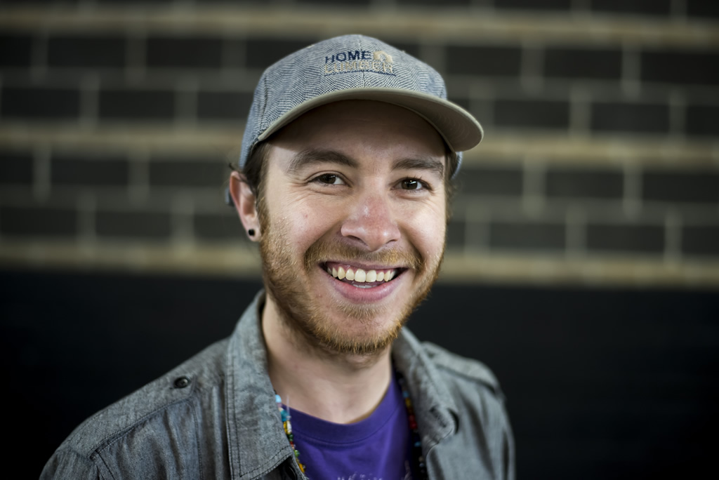 Man with light brown beard and a gray baseball cap in purple Atlantis shirt looking at camera smiling