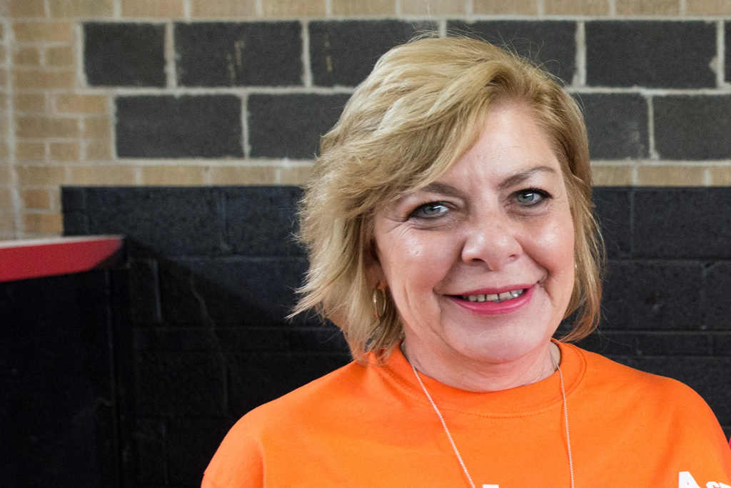 Woman with short blonde hair in orange ADAPT shirt looking at camera smiling