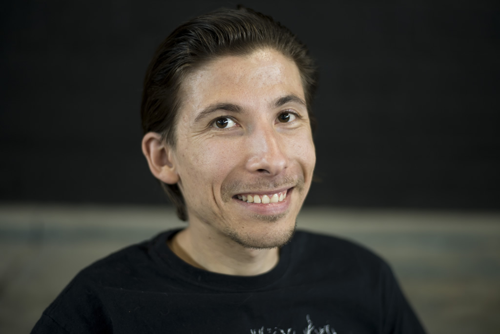 Man in a wheel chair with short combed black hair in black Atlantis shirt looking at camera smiling