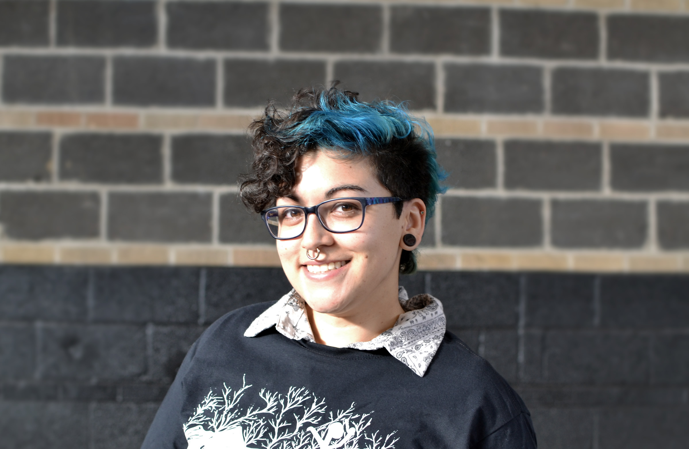 Woman with black and blue hair, black glasses, and a silver nose ring angled toward camera and smiling.